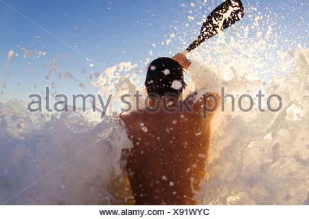 Young man kayaking on high wave, Sun Coast Beach, Durban, KwaZulu-Natal Province, South Africa - Stock Photo