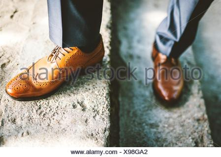Low Section Of Man With Brogue Shoes Standing On Steps - Stock Photo