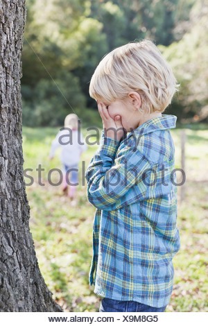 Children playing hide and seek outdoors - Stock Photo