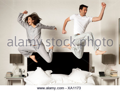 couple leaping out of bed - Stock Photo