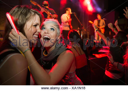 Enthusiastic women in crowd at music concert - Stock Photo