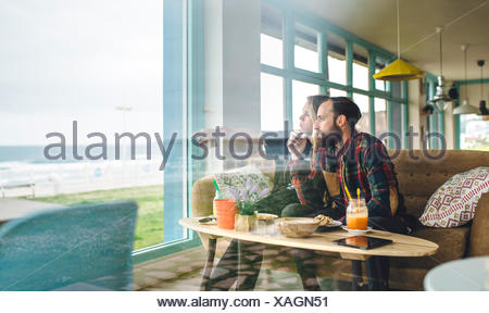 Spain, Asturias, Couple enjoying the seascape through the cafe window while having a brunch - Stock Photo