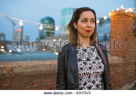 Smiling woman looking away on urban rooftop - Stock Photo