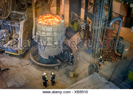 High angle view of steel workers inspecting molten steel in flask - Stock Photo