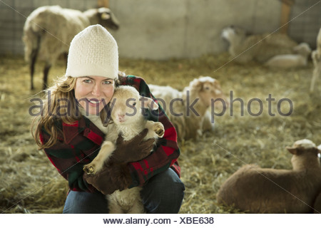 An Organic Farm in Winter in Cold Spring New York State A family working caring for the livestock A woman holding a small lamb - Stock Photo