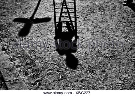 Shadow of a child playing in a playground - Stock Photo