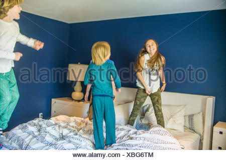 Teenage girl jumping on bed with younger brothers - Stock Photo