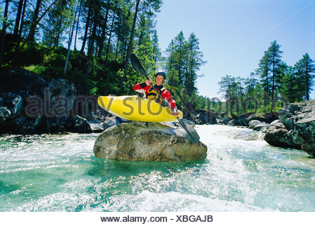Kayaker on top of rock in rapids smiling - Stock Photo