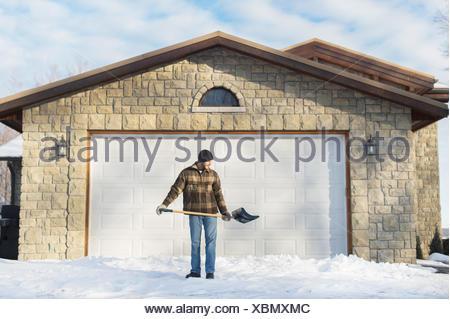 Man shoveling snow, Young's Point, Ontario, Canada - Stock Photo