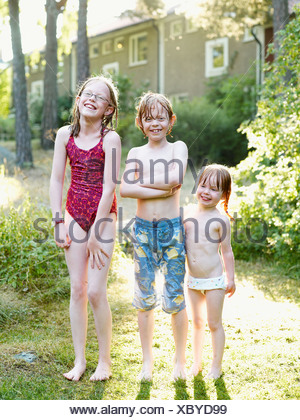 Wet brother and two sister standing in garden - Stock Photo