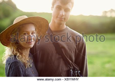 Portrait of romantic young couple in rural field - Stock Photo