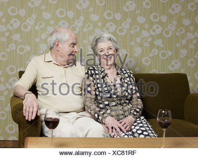 Senior couple relaxed on couch with two glasses of wine on the table - Stock Photo