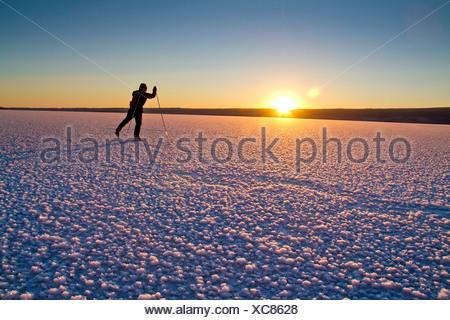 Man Nordic ice skating on frozen Skilak Lake, Kenai Peninsula, Southcentral Alaska, Winter - Stock Photo