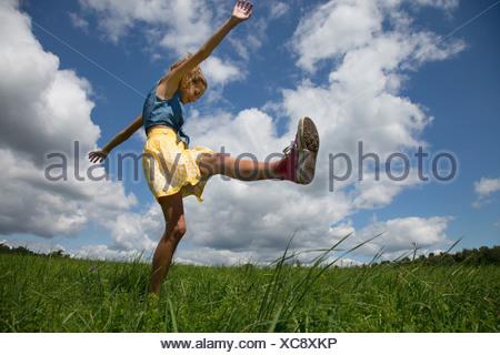 Teenage girl kicking leg in field - Stock Photo