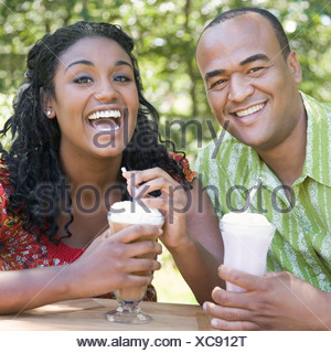 Portrait of a mid adult man drinking milkshake with a young woman - Stock Photo