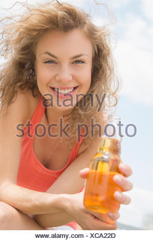 Portrait of young woman holding bottle of beer - Stock Photo