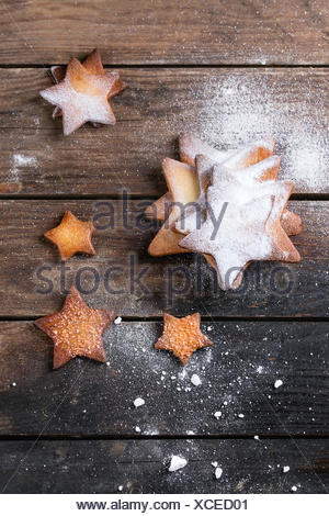 Homemade shortbread star shape sugar cookies different size with sugar powder on dark wooden surface. Christmas treats backgroun - Stock Photo