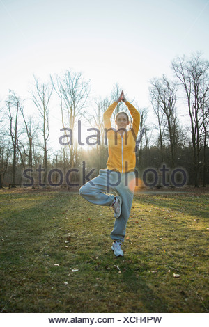 Young woman practicing yoga in field - Stock Photo