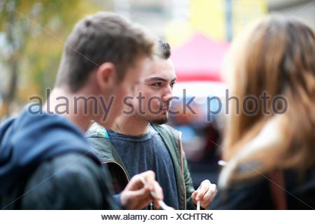 Group of young adults eating takeaway food, outdoors - Stock Photo