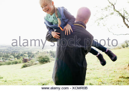 Father carrying daughter in arms - Stock Photo