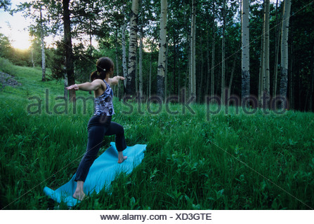 Young woman practicing yoga in Banff National Park, Alberta, Canada - Stock Photo