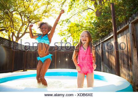 Two girls jumping in garden paddling pool - Stock Photo