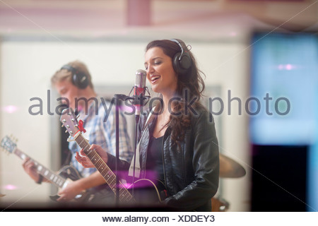 Young band playing music in recoding studio - Stock Photo