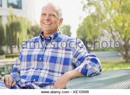 Portrait of senior man sitting outdoors - Stock Photo