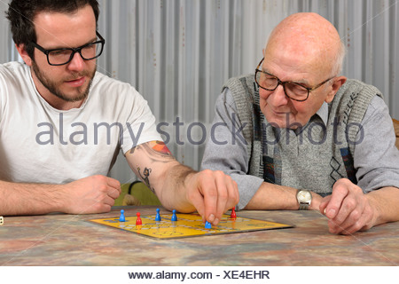 Grandfather and grandson playing together ludo at home - Stock Photo