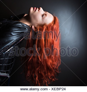 Pretty redhead young woman wearing leather jacket leaning back in chair with long hair hanging down - Stock Photo