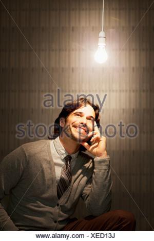 Smiling businessman sitting under illuminated light bulb - Stock Photo