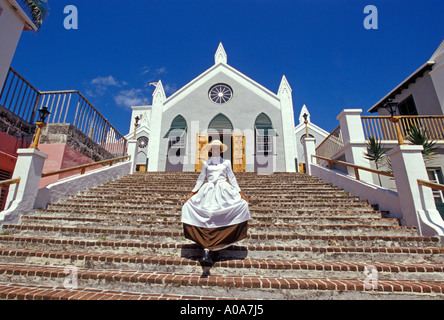 CARIBBEAN BERMUDA Town of St George Woman im Zeitraum Kleid hinunter Schritte der St James Church - Stockfoto