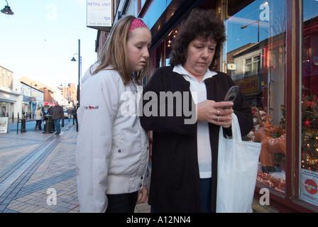 Mutter und Tochter mit Handy in Straße England UK United Kingdom GB Großbritannien EU Europäische Union Europa - Stockfoto