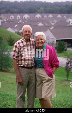 Eine aktive senior paar posiert auf einem Hügel mit Blick auf ihre Pensionierung Gemeinschaft in Maryland Modell - Stockfoto