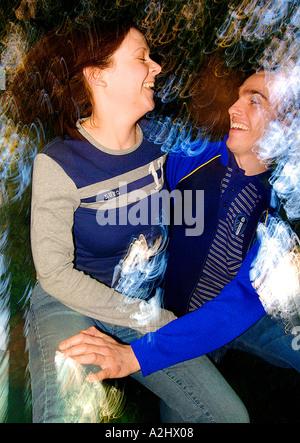 Mann und Frau, Alter 20-25 in einer liebevollen Umarmung. Das Bild ist in Farbe und Bewegungsunschärfe. - Stockfoto