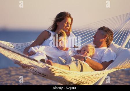 Mutter Vater und seinen zwei Kindern zusammen in einer Hängematte am Strand liegen - Stockfoto