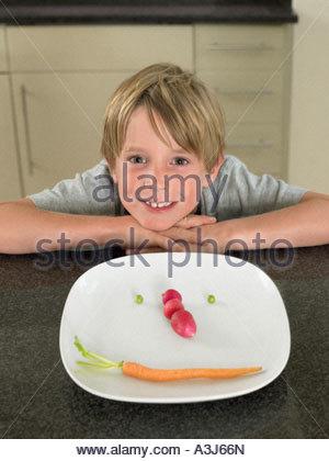 Junge mit Gemüse Gesicht auf einem Teller - Stockfoto