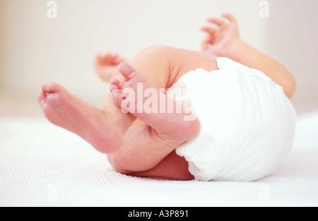Neugeborenes Baby auf Rücken versuchen, über Rollen - Stockfoto