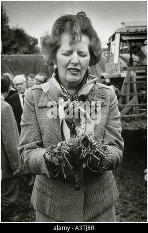 Frau Thatcher komischen Gesicht ziehen, wie sie Gülle auf einem Bauernhof abholt - Stockfoto