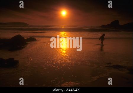 Silhouette Form ein Kind paddeln, im seichten Wasser am Strand Cornish im Vereinigten Königreich. - Stockfoto