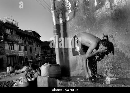 Ein Mann nimmt eine Dusche auf der Straße das ländliche Dorf Bungamati außerhalb von Kathmandu in Nepal - Stockfoto