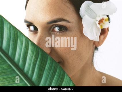 Frau mit Orchidee hinter Ohr, Palmblatt teilweise bedeckte Gesicht, Nahaufnahme - Stockfoto