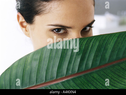 Frau, Blick in die Kamera, Palmblatt teilweise bedeckte Gesicht, Nahaufnahme - Stockfoto