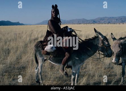 Himba Nomaden Frauen in traditionellen Lederbekleidung überqueren der Marienfluss auf Esel im Kaokoland Norden Namibias - Stockfoto