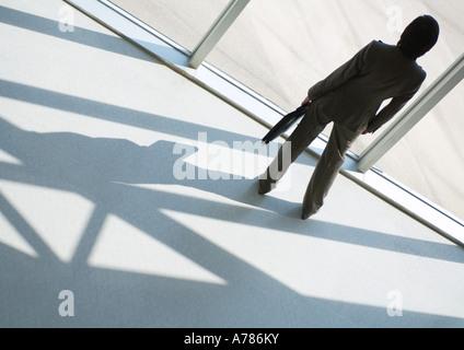 Geschäftsfrau, Blick aus dem Fenster, in voller Länge, hoher Winkel Rückansicht - Stockfoto