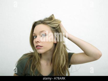 Teenager-Mädchen Haar zurückschieben und Blick in die Kamera, Porträt - Stockfoto