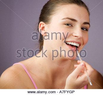 Ein junges Mädchen Lipgloss auftragen - Stockfoto