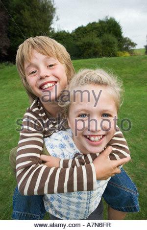 Mädchen 9 11 tragen Boy 8 10 von Piggyback in großen Land Garten lächelnd Nahaufnahme portrait - Stockfoto