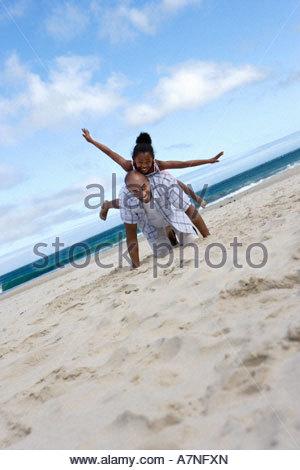 Mädchen 7 9 balancieren auf Vaters zurück am Strand Arme ausgestreckt Porträt Oberfläche Ebene kippen - Stockfoto