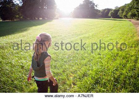 Blonde Mädchen 7 9 Fuß in Feld in hellem Sonnenlicht Rückansicht Bäume im Hintergrund lens Flare - Stockfoto